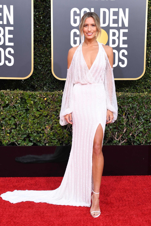 La conductora de televisión australiana Rene Bargh invitada a los Golden Globes lució un diseño de J.Andreatta con mangas japonesas, escote V, hombros al descubierto y gran tajo en color blanco de paillettes. Completó el look con sandalias a tono