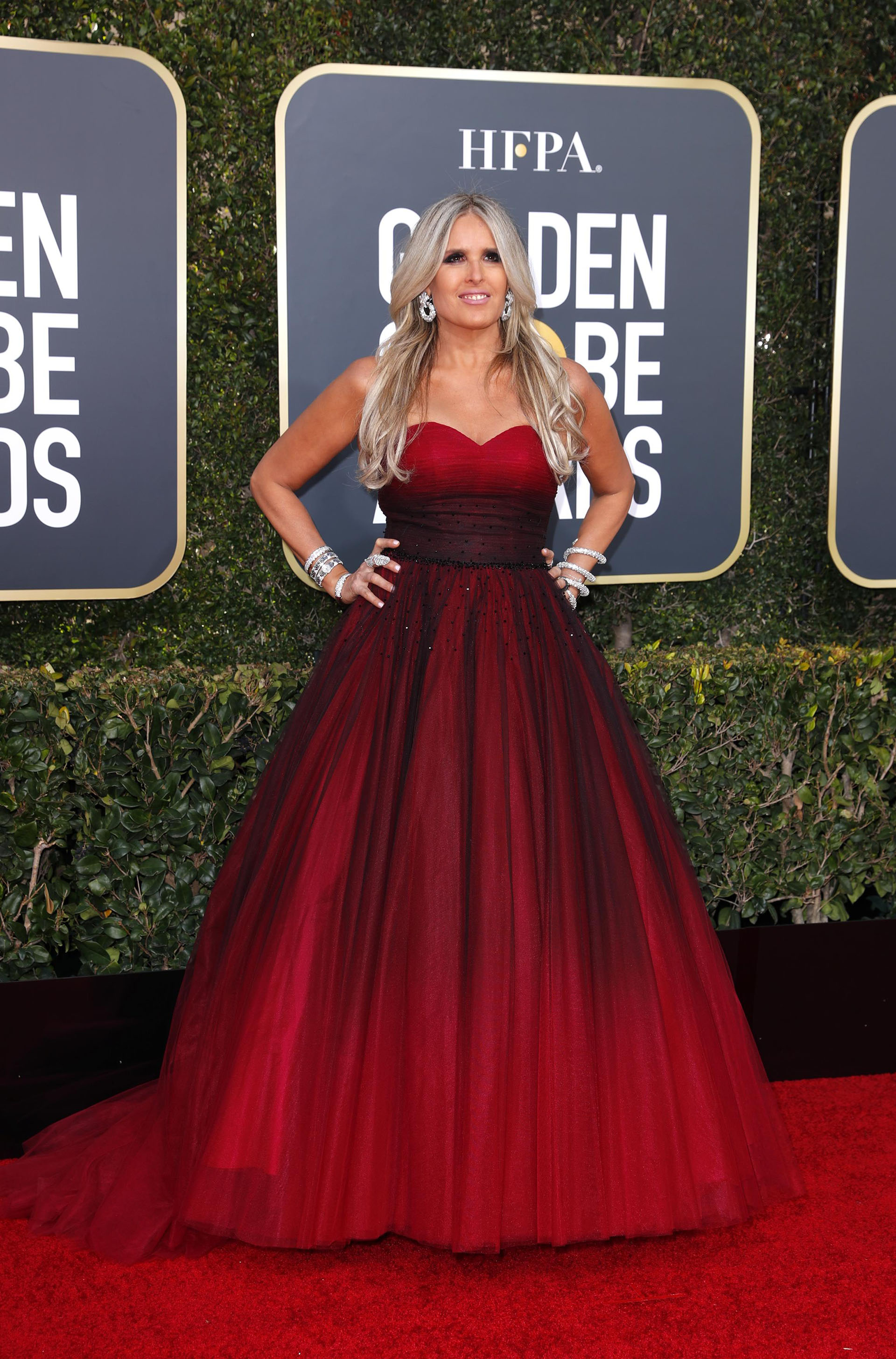 Tiziana Rocca enfundada en un vestido con diseño princesa de tul. Combinado con puntilla en negro y rojo con escote corazón. Completó su look con accesorios plateados, brazaletes, esclavas y aros colagantes