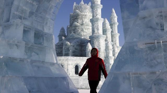 Un visitante camina frente a esculturas de hielo en el festival anual de hielo en Harbin