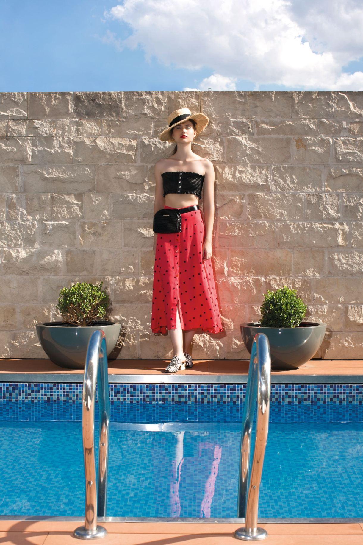 Top de cuerina elastizado y sombrero de rafia ($ 1.990 y $ 1.590, Las Pepas), riñonera y chinelas trenzadas ($ 2.200 y $ 4.900, Uma) y pollera con lunares ($ 2.475, La Cofradía).