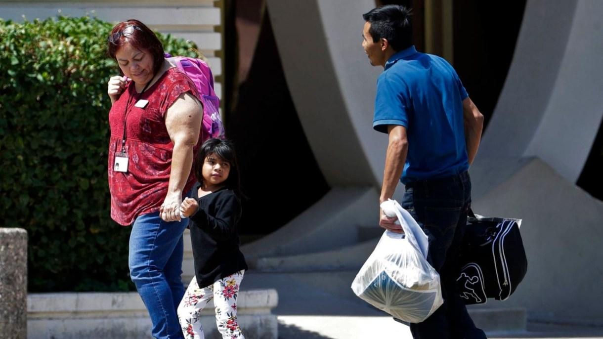 Un niño migrante toma la mano de un trabajador de Servicios Sociales Luteranos que ayuda a reunir a niños separados de sus padres, el 26 de julio de 2018. (Foto: Matt York / AP)