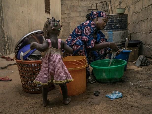 Hajara, quien divorció de su marido y volvió a vivir con su familia, lava los platos al lado de su hija en Maradí (Laura Boushnak/The New York Times)