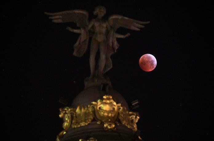 "La luna detrás de la estatua de la""Victoria Alada"" del edificioMetropolien Madrid(REUTERS/Sergio Perez)"