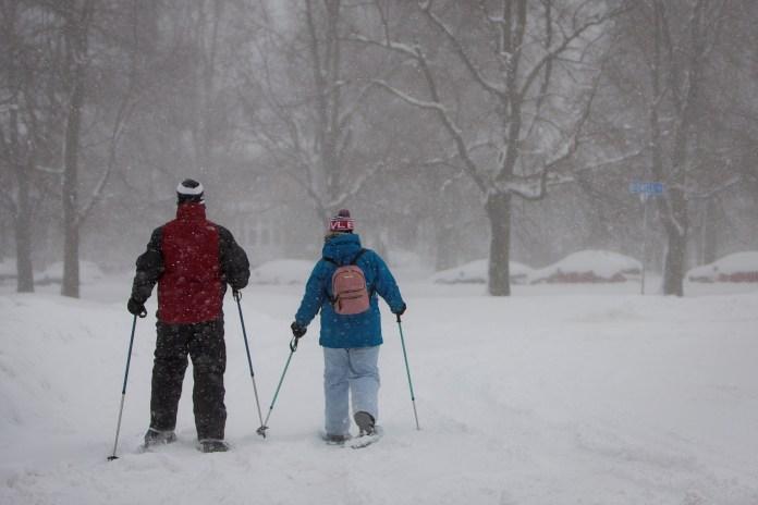 Un hombre y una mujer caminan con esquíes por otra calle de Buffalo, al noroeste del estado de Nueva York