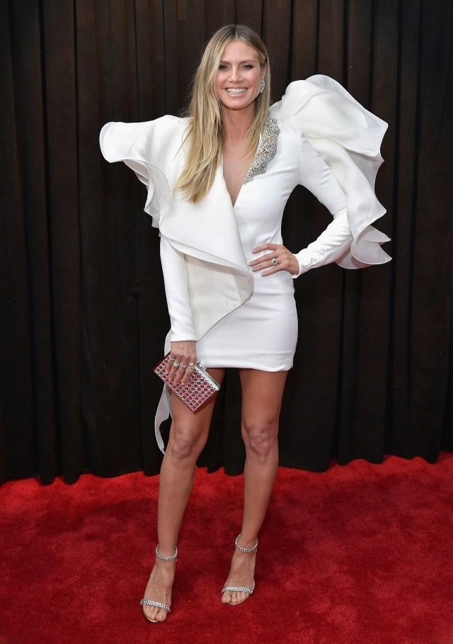 Heidi Klum en blanco y plateado. Un mini vestido con mangas y volados que simulaban ser alas. Completó el look con sandalias y clutch rígido. Joyas: anillos y aros de brillantes
