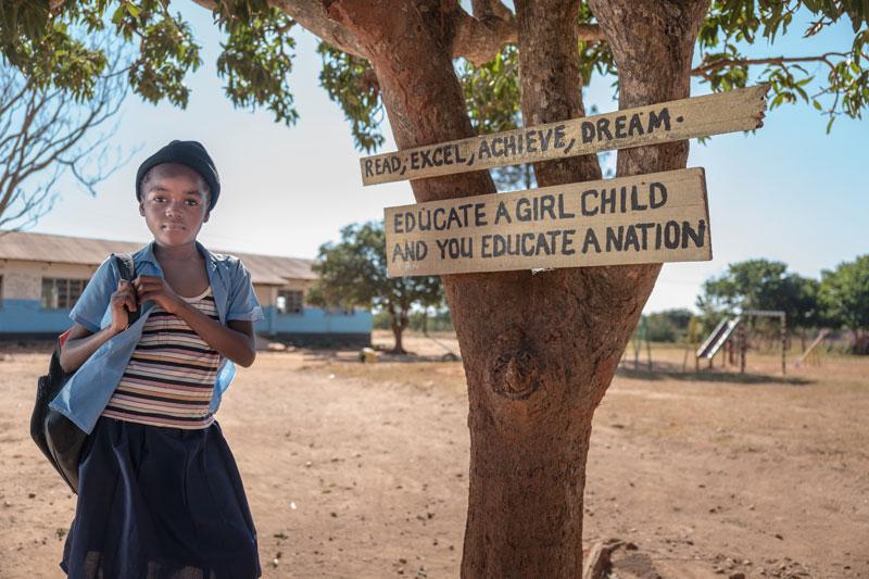 """Una estudiante de primaria en Zambia. En el árbol, la leyenda """"Lee, destácate, ten éxito, sueña. Educa a una niña y educarás un país"""" (Bill and Melinda Gates Foundation)"""