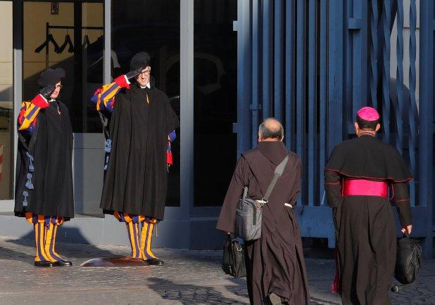 Guardias suizos saludan a dos participantes de la cumbre en el Vaticano (REUTERS/Remo Casilli)