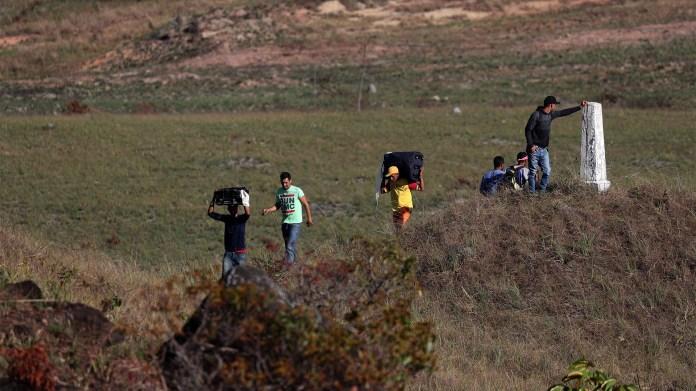 Venezolanos cruzan la frontera entre su país y Colombia desde otro punto de la ciudad de Ureña, con cajas de comida y medicamentos (Reuters)