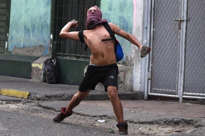 Un hombre arroja piedras a los guardias nacionales venezolanos en la ciudad fronteriza de Ureña (AFP)