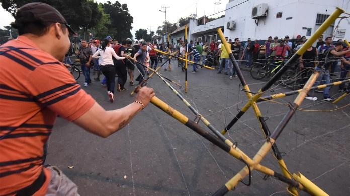 Los venezolanos intentan desmantelar una barrera en la ciudad fronteriza de Ureña después de que el gobierno de Maduro ordenara cerrar temporalmente la frontera con Colombia (AFP)