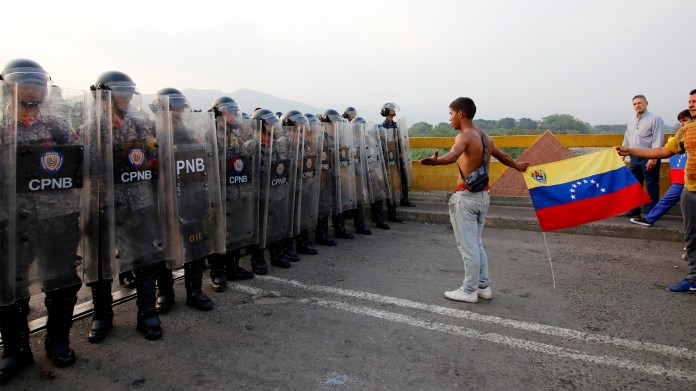 Los venezolanos se enfrentan a guardias nacionales que les exigen que dejen la ayuda humanitaria en el puente Simón Bolívar, en Cúcuta, Colombia, después de que el gobierno del presidente Nicolás Maduro ordenara el cierre temporal de la frontera con Colombia (AFP)