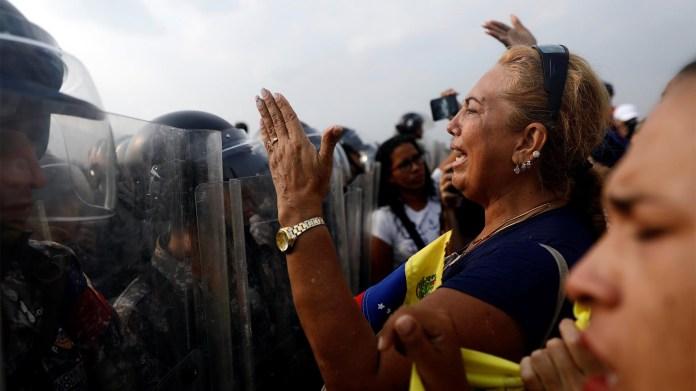 Los partidarios de la oposición venezolana exigen cruzar la línea fronteriza entre Colombia y Venezuela en el puente Simón Bolívar cuando las fuerzas de seguridad de Venezuela se paran en la línea fronteriza bloqueando su camino en las afueras de Cúcuta, Colombia (Reuters)