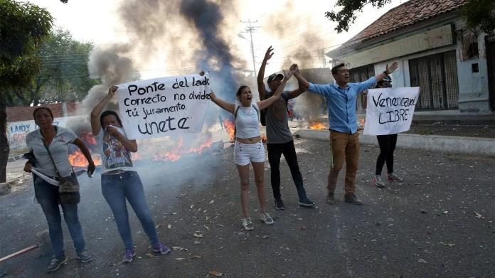 """""""Ponte del lado correcto, no olvides tu juramento, únete"""", son algunas de las banderas que los venezolanos le muestran a las fuerzas de seguridad chavistas para que abran el paso fronterizo con Colombia (Reuters)"""