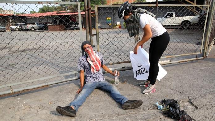 Un manifestante trata de reponerse luego de enfrentar a las fuerzas de seguridad de Nicolás Maduro (Reuters)