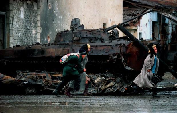 Civiles chechenos corren frente a un tanque ruso destruido en Grozny, durante un enfrentamiento en enero de 1995