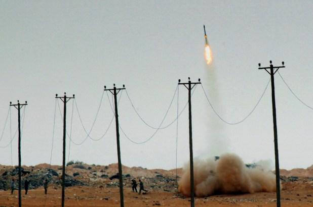 Milicianos corren tras lanzar un cohete contras las fuerzas de Muammar Khadafi en Libia, en abril de 2011