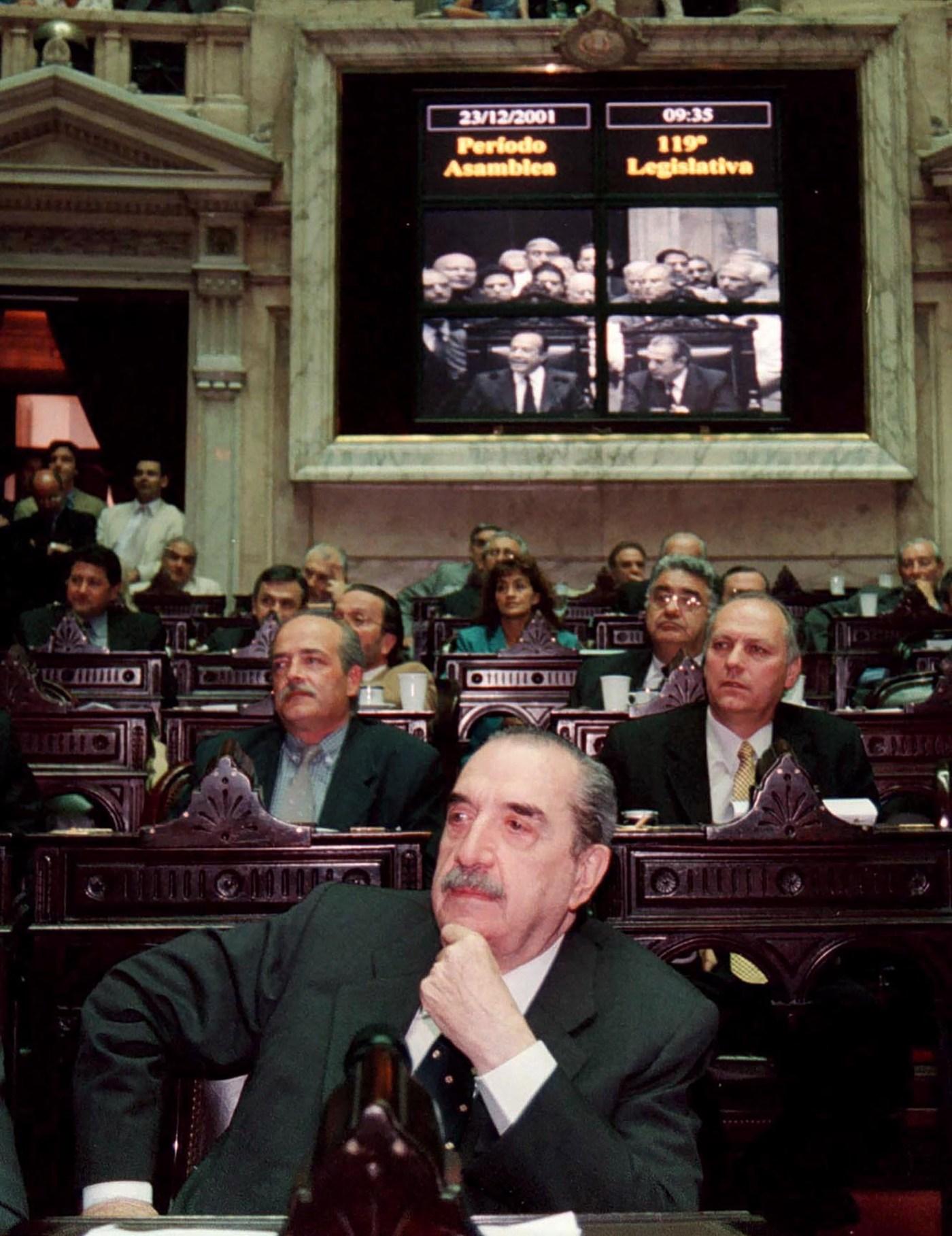 A fines de 2001 ex presidente escucha los anuncios del flamante presidente, Adolfo Rodríguez Saá, luego de la ceremonia de juramento realizada en el recinto del Congreso