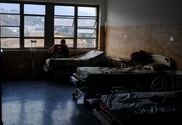 Un paciente observa por la ventana de un hospital sin luz (AFP)