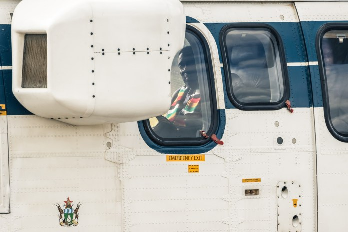 El presidente de Zimbabwe, Emmerson Mnangagwa, se sienta en un helicóptero al llegar a Mutare, provincia de Manicaland, antes de recorrer las áreas devastadas por el ciclón Idai en Chimanimani, el 19 de marzo. (Photo by Jekesai NJIKIZANA / AFP)