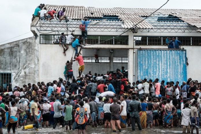"""Las personas participan en los saqueos de arroz chino impresos con el sello """"China Aid"""" de un almacén que quedó rodeado de agua después del impacto del ciclón en Beira (Photo by Yasuyoshi CHIBA / AFP)"""