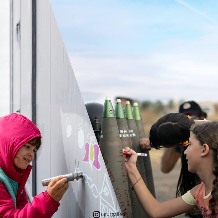 Una niña escribe un grafitti en un campo de refugiados de Grecia y otros niños escriben mensaje en una bomba durante la guerra entre Israel y Líbano en 2006
