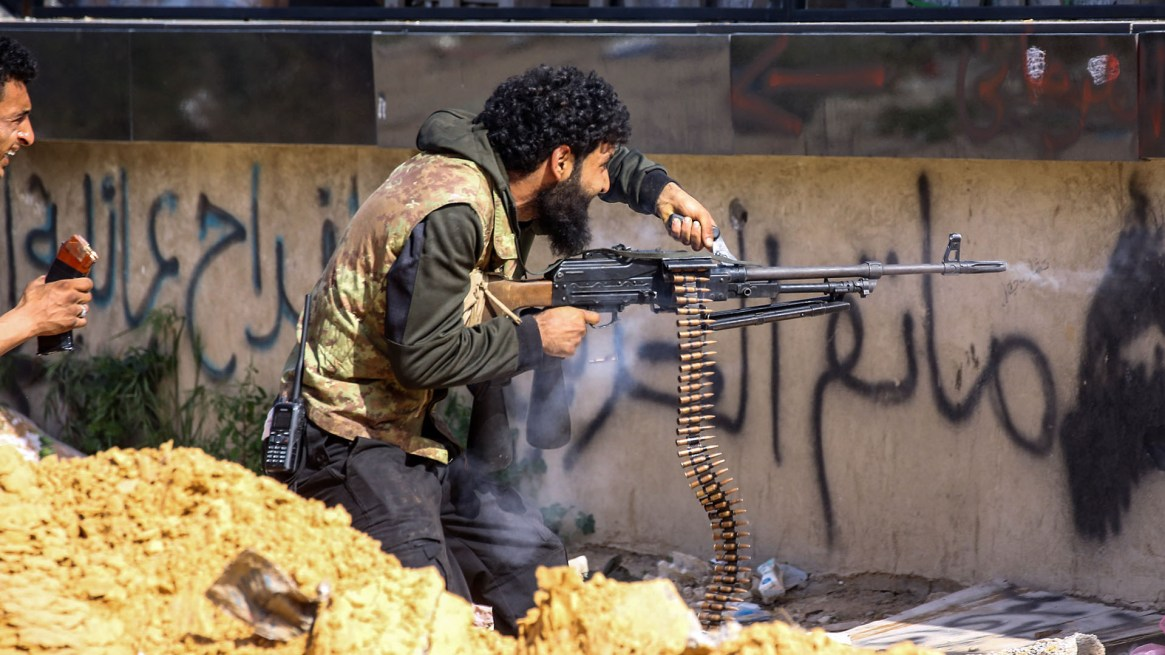 Un combatiente leal al Gobierno de Acuerdo Nacional dispara una ametralladora durante los enfrentamientos con las fuerzas de Haftar en el suburbio de Aoli Zara, en Trípoli, el 10 de abril (AFP)
