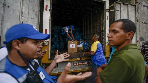 En el barrio de Catia, en Caracas, cooperantes de la Cruz Roja entregaron bidones para el acopio de agua así como pastillas potabilizadoras (AFP)
