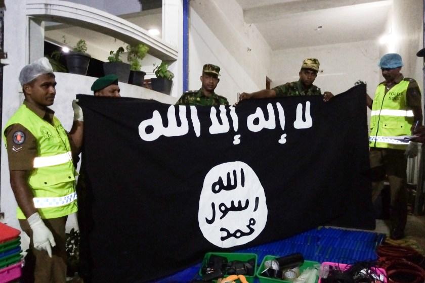 Las autoridades con una bandera del ISIS que fue incautada durante allanamientos.(Photo by STRINGER / AFP)