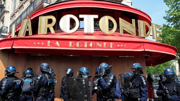 La policía antidisturbios francesa se para frente a los paneles de madera que protegen el restaurante La Rotonde, muy identificado con Emmanuel Macron (Reuters)