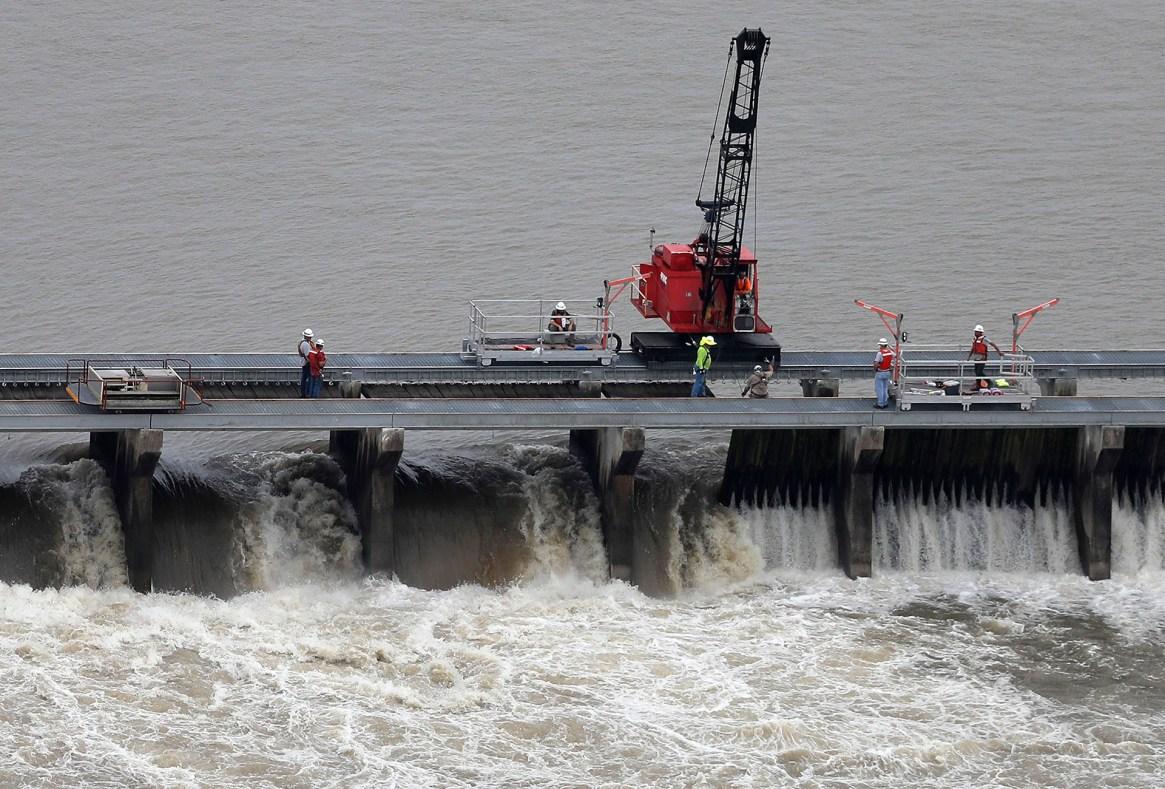 Los trabajadores abren las compuertas del Bonnet Carre Spillway, para desviar el agua del río Misisipi al lago Pontchartrain, río arriba de Nueva Orleans, en Norco, Luisiana, el viernes 10 de mayo de 2019. (AP)