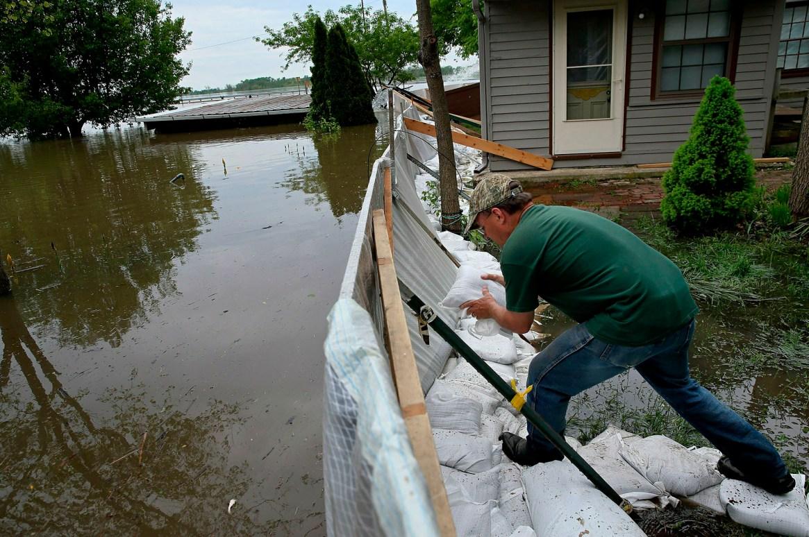 Alley Ringhausen utiliza bolsas de arena para reforzar el muro que él y otros voluntarios construyeron alrededor de la Riverview House en Elsah, Illinois, a medida que el agua de la inundación del río Misisipi se filtra a través de una barrera improvisada el lunes 6 de mayo de 2019. (AP)