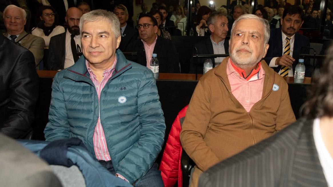 Lázaro Báez -campera verde- y Julio De Vido -campera marrón- también están sentados en el banquillo de los acusados