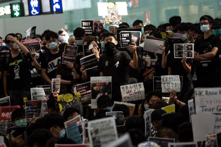 Un grupo de manifestantes a favor de la democracia muestra eslóganes frente a la sala de embarque(Foto de Philip FONG / AFP)