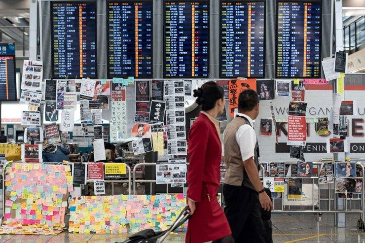 El 13 de agosto de 2019, al día siguiente de que el aeropuerto de Hong Kong cerrara sus puertas debido a las protestas a favor de la democracia, dos azafatas pasan por delante de un tablero de anuncios eléctrico cubierto de carteles (Foto de Philip FONG / AFP)