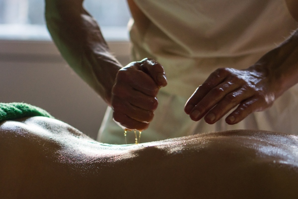 A massage therapist performing panchakarma therapy, panchakarma treatment. What does panchakarma cost?