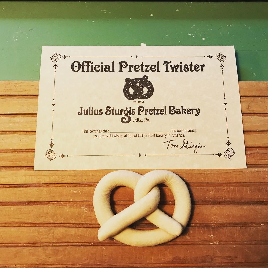Photo by user eddiev9, caption reads I'm a certified Pretzel 🥨 twister .  #juliussturgis #tomsturgis #lititzpa #factorytours #pretzels
