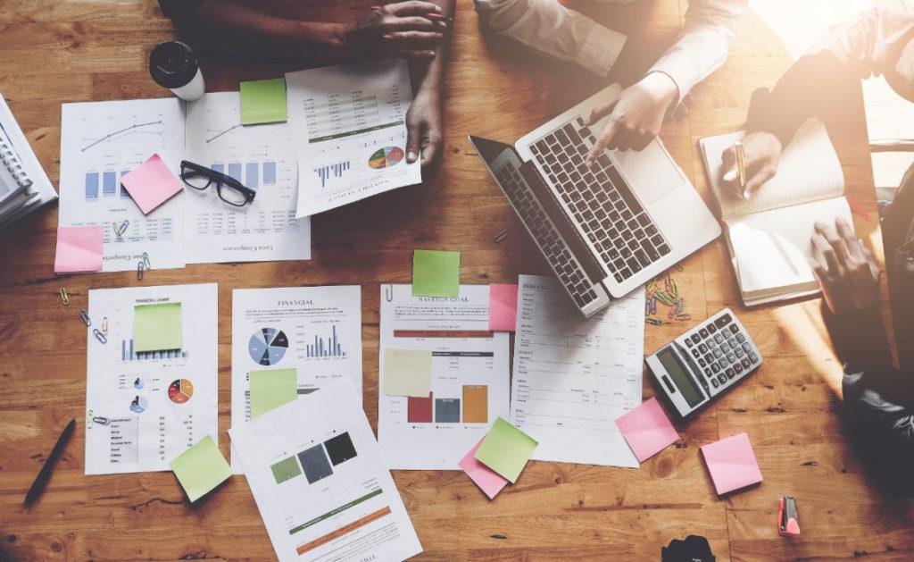 imagem de pessoas mexendo no notebook e varios papeis com gráficos analisando as diferenças entre Inbound e Outbound Marketing