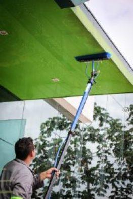 Homem limpando fachada