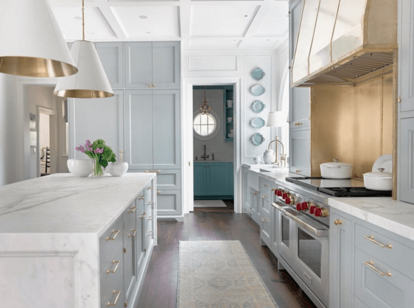 Pale blue kitchen cabinets, white marble counters, gold vent hood, Circa Lighting pendants