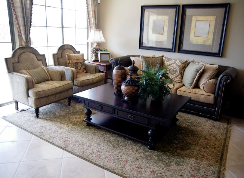 A traditional living room with a light tile floor and an ornate floral rug and tall windows on the rear wall. All of the furniture has nailhead trim accents and a delicate floral pattern. Accents include pictures, urns, and a houseplant.