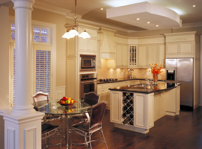 Innovative lighting, peeking from a ceiling detail, trio of pendant lights, and under-cabinet hardware, makes this entire kitchen glow. Dark hardwood flooring contrasts with white cabinetry and tile backsplash.