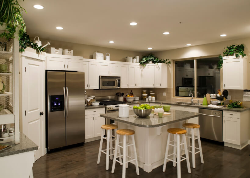 In this cozy U-shaped kitchen, a granite topped island stands surrounded by pristine white cabinetry over a dark hardwood floor. Beige walls and tile backsplash aid the brightness, while stainless steel appliances maintain the modern tone.