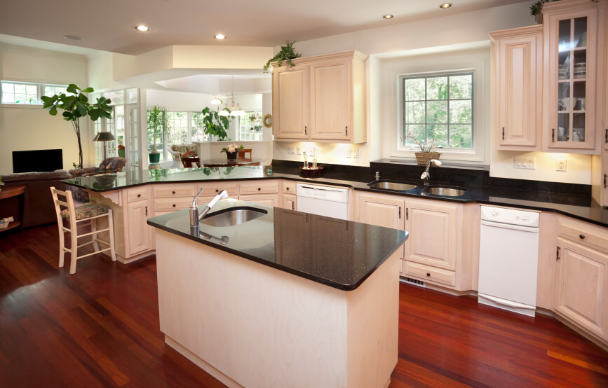 In a large open-plan space shared with a living room, this kitchen is defined by its black countertops and white cabinetry. The warm glow of rich hardwood flooring adds a lived-in feel.