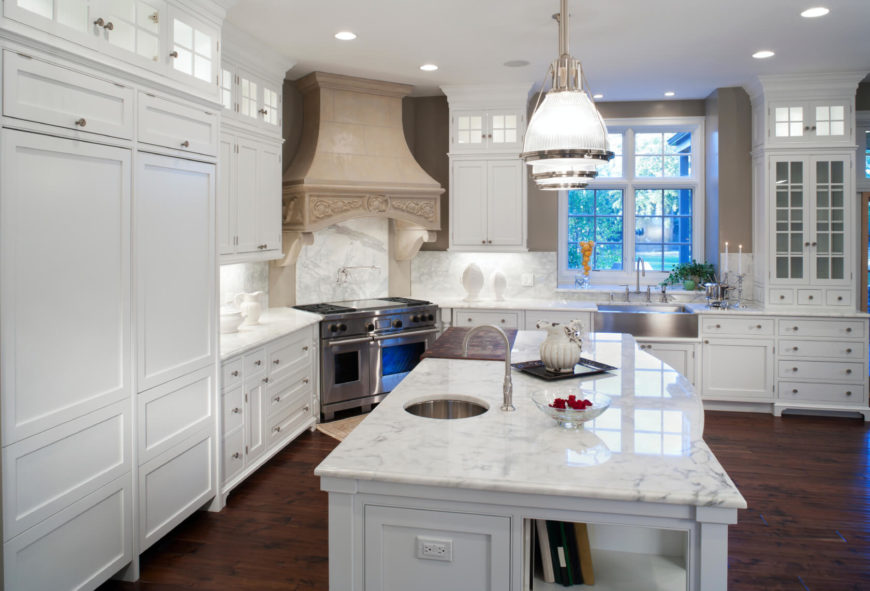 The large island with white marble countertop is the centerpiece in this expansive kitchen, flush with white cabinetry over a dark stained hardwood floor. The window design is mirrored in glass door cupboards.