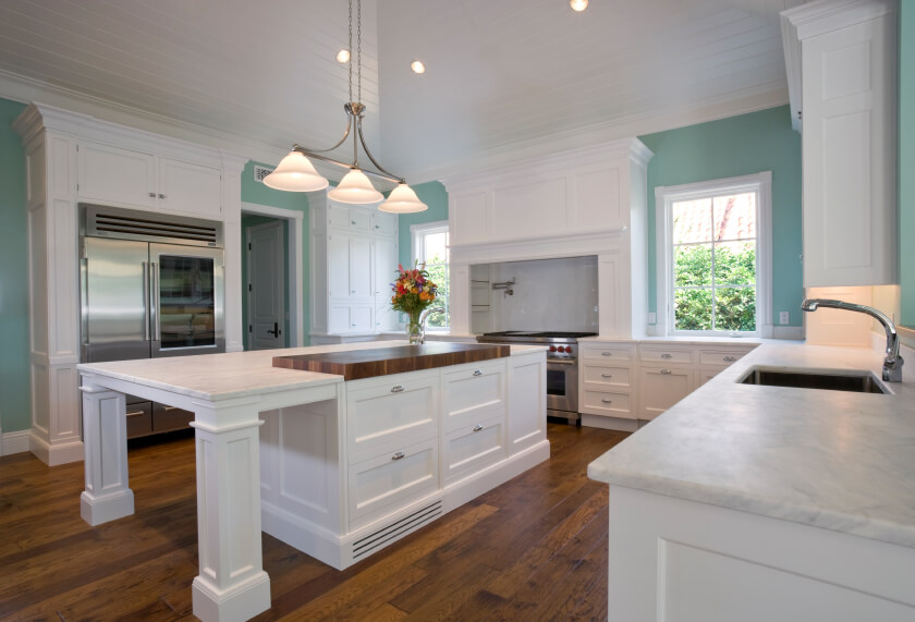 Sharp lines and high contrast define this ultra-modern kitchen. The massive island at center stands in bold white, matching the cabinetry throughout as it pairs with light blue walls and a hardwood floor. The island and all countertops are covered in white marble.