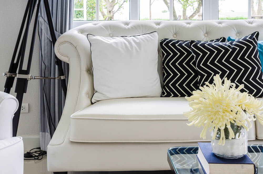 White sofa with a white pillow and black pillow with white crooked lines. The black/white pillows make this sofa pillow arrangement pop.
