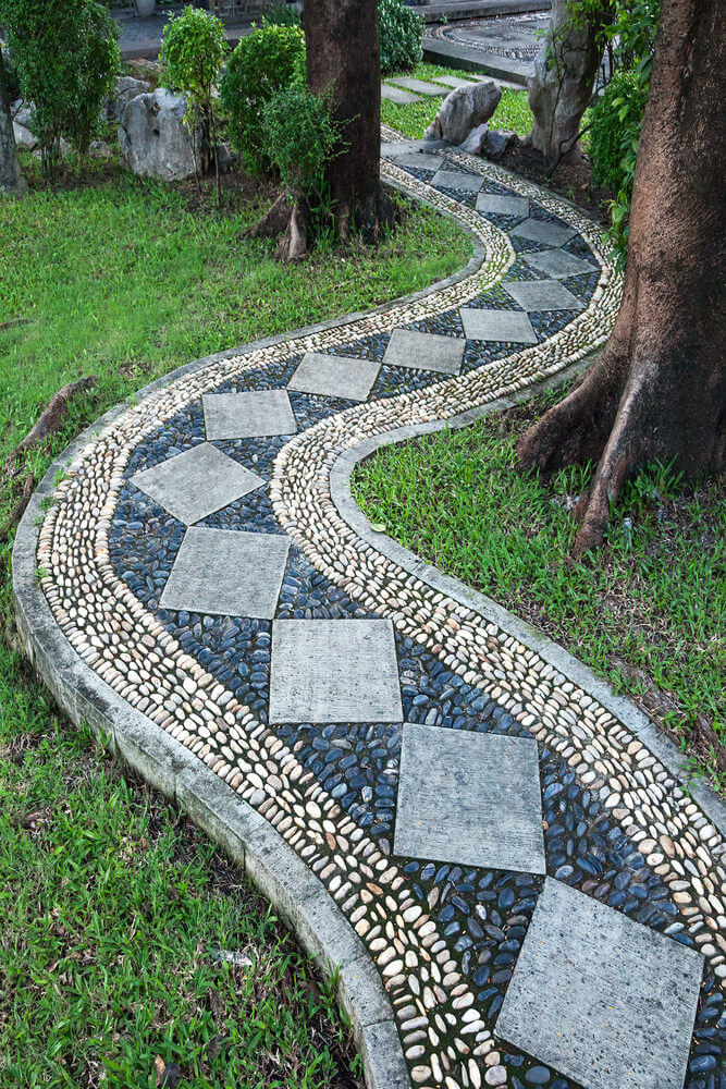 A curving pathway with diamond pavers filled with blue and white stones is making its way through the trees and is connected with rectangular pavers on the end.