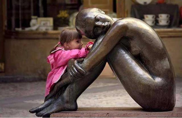 niña contando un secreto a una estatua