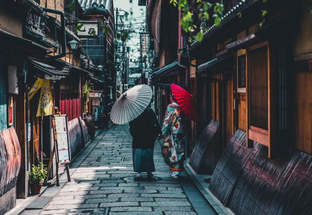 Women in traditional dress walking down a street in Kyoto, Japan