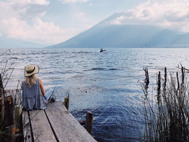 A woman in a straw hat sitting at the edge of a lake looking up at a nearby mountain